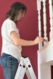 Νέα όμορφη γυναίκα που χρωματίζει ένα λευκό προεξοχών ballustrade με μια βούρτσα στοκ εικόνες