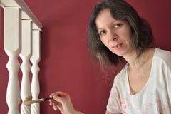 Νέα όμορφη γυναίκα που χρωματίζει ένα λευκό προεξοχών ballustrade με μια βούρτσα στοκ εικόνες με δικαίωμα ελεύθερης χρήσης