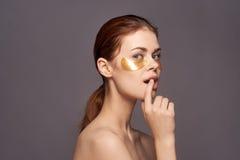 Νέα όμορφη γυναίκα σε ένα γκρίζο υπόβαθρο, φροντίδα δέρματος ματιών, ομορφιά, υγεία στοκ φωτογραφίες
