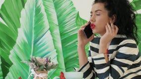 Νέα, όμορφη γυναίκα σε ένα ριγωτό κοστούμι που μιλά στο τηλέφωνο στο υπόβαθρο των πράσινων φύλλων απόθεμα βίντεο