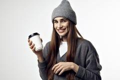 Νέα όμορφη γυναίκα σε μια γκρίζα εξάρτηση με ένα φλιτζάνι του καφέ εγγράφου Πάρτε μαζί τη συσκευασία για το σχεδιάγραμμα Στοκ εικόνα με δικαίωμα ελεύθερης χρήσης