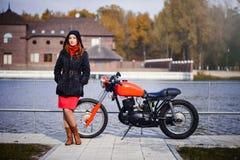 Νέα όμορφη γυναίκα σε μια κουκούλα στην κρύα εποχή ενάντια σε μια κόκκινη μοτοσικλέτα και μια κίτρινη δασική, κόκκινη τρίχα και έ στοκ φωτογραφία με δικαίωμα ελεύθερης χρήσης