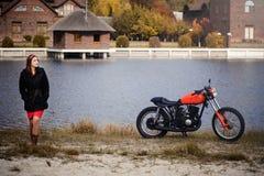 Νέα όμορφη γυναίκα σε μια κουκούλα στην κρύα εποχή ενάντια σε μια κόκκινη μοτοσικλέτα και μια κίτρινη δασική, κόκκινη τρίχα και έ στοκ εικόνα