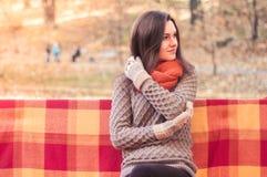 Νέα όμορφη γυναίκα σε μια πλεκτή συνεδρίαση πουλόβερ σε έναν πάγκο σε ένα πάρκο φθινοπώρου Στοκ φωτογραφίες με δικαίωμα ελεύθερης χρήσης