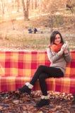 Νέα όμορφη γυναίκα σε μια πλεκτή συνεδρίαση πουλόβερ σε έναν πάγκο σε ένα πάρκο φθινοπώρου Στοκ εικόνα με δικαίωμα ελεύθερης χρήσης