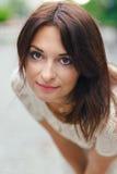 Νέα όμορφη γυναίκα, σκοτεινός-μαλλιαρός, χαμογελώντας, κοιτάζοντας αδιάκριτα στο πλαίσιο, που επισκέπτεται το κέντρο πόλεων μια η Στοκ Εικόνες