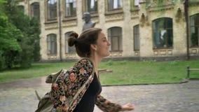 Νέα όμορφη γυναίκα σπουδαστής που τρέχει αργά στις κατηγορίες σε πανεπιστημιακό και που μιλά στο τηλέφωνο, που περπατά στην οδό π απόθεμα βίντεο