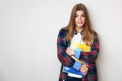Νέα όμορφη γυναίκα σπουδαστής με τα βιβλία που στέκονται ενάντια στον τοίχο Στοκ εικόνες με δικαίωμα ελεύθερης χρήσης