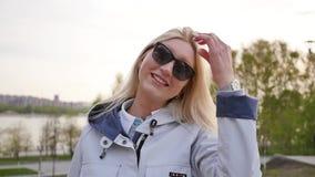 Νέα όμορφη γυναίκα στα γυαλιά ηλίου Αρκετά ξανθός σε έναν περίπατο o φιλμ μικρού μήκους