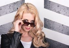 Νέα όμορφη γυναίκα στα γυαλιά ηλίου Εξετάστε τη φωτογραφική μηχανή Μακριά κυματιστά τρίχα και Makeup Στοκ Εικόνες