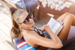 Νέα όμορφη γυναίκα στα γυαλιά ηλίου που κάθονται κοντά στην παραλία, που έχουν, που χαμογελούν και που διαβάζουν το βιβλίο κατά τ στοκ εικόνες