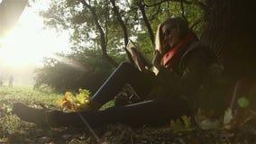 Νέα όμορφη γυναίκα στα γυαλιά ηλίου με τον υπολογιστή ταμπλετών στο όμορφο πάρκο φθινοπώρου φιλμ μικρού μήκους
