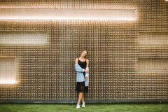 Νέα όμορφη γυναίκα στα πλαίσια ενός ασυνήθιστου ξύλινου τοίχου στοκ εικόνες με δικαίωμα ελεύθερης χρήσης