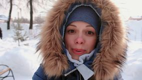 Νέα όμορφη γυναίκα στην κουκούλα γουνών που μιλά στην τηλεοπτική σύνδεση και που περπατά στο πάρκο χειμερινών πόλεων στη χιονώδη  απόθεμα βίντεο