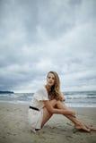 Νέα όμορφη γυναίκα στην κρύα θυελλώδη παραλία Στοκ Φωτογραφία