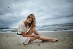 Νέα όμορφη γυναίκα στην κρύα θυελλώδη παραλία Στοκ Φωτογραφίες