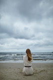 Νέα όμορφη γυναίκα στην κρύα θυελλώδη παραλία Στοκ φωτογραφία με δικαίωμα ελεύθερης χρήσης