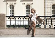 Νέα όμορφη γυναίκα στην μπεζ τοποθέτηση παλτών υπαίθρια στο ηλιόλουστο wea Στοκ εικόνες με δικαίωμα ελεύθερης χρήσης
