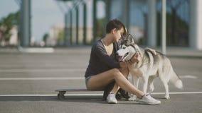 Νέα όμορφη γυναίκα στην οδό που αγκαλιάζει τη γεροδεμένη συνεδρίαση σκυλιών της skateboard ή longboard φιλμ μικρού μήκους