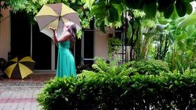 Νέα όμορφη γυναίκα στην πράσινη ομπρέλα εκμετάλλευσης φορεμάτων έξω στη βροχερή ημέρα Το κορίτσι απολαμβάνει με τη βροχή 3840x216 απόθεμα βίντεο