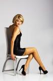 Νέα όμορφη γυναίκα στη μαύρη συνεδρίαση φορεμάτων σε μια καρέκλα Στοκ Φωτογραφίες