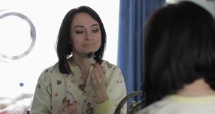 Νέα, όμορφη γυναίκα στις πυτζάμες κοντά στον καθρέφτη Ομορφιά και makeup έννοια απόθεμα βίντεο