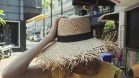 Νέα όμορφη γυναίκα στον περίπατο καπέλων αχύρου κατ' ευθείαν στη κάμερα και τα χαμόγελα απόθεμα βίντεο