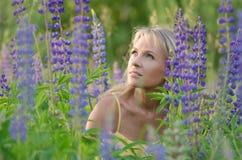 Νέα όμορφη γυναίκα στον τομέα lupine Στοκ φωτογραφία με δικαίωμα ελεύθερης χρήσης