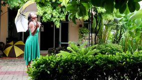 Νέα όμορφη γυναίκα στους πράσινους περιπάτους φορεμάτων στη βροχή με την ομπρέλα Το κορίτσι απολαμβάνει της βροχής 3840x2160 απόθεμα βίντεο