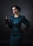 Νέα όμορφη γυναίκα στο αναδρομικό ύφος με το κόκκινο κρασί Στοκ φωτογραφία με δικαίωμα ελεύθερης χρήσης