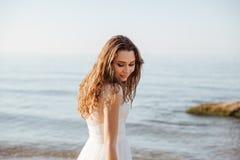 Νέα όμορφη γυναίκα στο γαμήλιο φόρεμα στην παραλία Στοκ Εικόνα