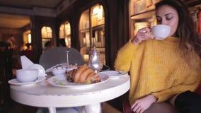 Νέα όμορφη γυναίκα στο κίτρινο πουλόβερ που έχει το πρόγευμα στον άνετο καφέ και που πίνει το τσάι φιλμ μικρού μήκους