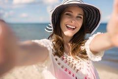 Νέα όμορφη γυναίκα στο καπέλο που φθάνει έξω στα χέρια της Στοκ Εικόνες