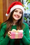 Νέα όμορφη γυναίκα στο κιβώτιο δώρων εκμετάλλευσης καπέλων santas Στοκ φωτογραφίες με δικαίωμα ελεύθερης χρήσης