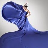 Νέα όμορφη γυναίκα στο κυματίζοντας μπλε φόρεμα Στοκ Φωτογραφίες