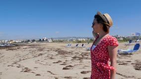 Νέα όμορφη γυναίκα στο κόκκινο φόρεμα και καπέλο που στέκεται μόνο στην κενή παραλία με τα sunbeds Παραλία άμμου με τα ισχυρούς κ απόθεμα βίντεο