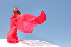 Νέα όμορφη γυναίκα στο κόκκινο φόρεμα πέρα από το bly ουρανό στοκ εικόνες με δικαίωμα ελεύθερης χρήσης