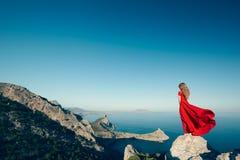 Νέα όμορφη γυναίκα στο κόκκινο φόρεμα που κοιτάζει στη θάλασσα βουνών Στοκ Φωτογραφία