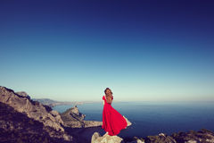 Νέα όμορφη γυναίκα στο κόκκινο φόρεμα που κοιτάζει στη θάλασσα βουνών Στοκ εικόνα με δικαίωμα ελεύθερης χρήσης