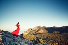 Νέα όμορφη γυναίκα στο κόκκινο φόρεμα που κοιτάζει στη θάλασσα βουνών Στοκ φωτογραφία με δικαίωμα ελεύθερης χρήσης