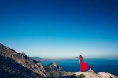 Νέα όμορφη γυναίκα στο κόκκινο φόρεμα που κοιτάζει στη θάλασσα βουνών Στοκ Εικόνα