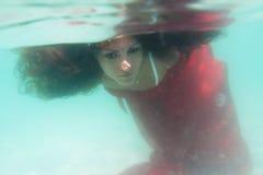 Νέα όμορφη γυναίκα στο κόκκινο φόρεμα υποβρύχιο στοκ φωτογραφίες