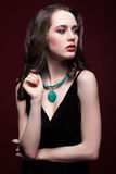Νέα όμορφη γυναίκα στο μαύρο φόρεμα με το πράσινο χρώμα φυστικιών Στοκ φωτογραφία με δικαίωμα ελεύθερης χρήσης