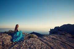 Νέα όμορφη γυναίκα στο μπλε φόρεμα που κοιτάζει στη θάλασσα βουνών Στοκ φωτογραφία με δικαίωμα ελεύθερης χρήσης