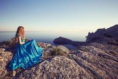 Νέα όμορφη γυναίκα στο μπλε φόρεμα που κοιτάζει στη θάλασσα βουνών Στοκ Εικόνες