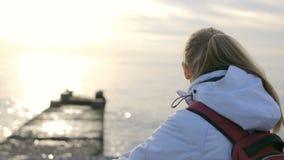 Νέα όμορφη γυναίκα στο σακάκι με τη συνεδρίαση σακιδίων πλάτης κοντά στη θάλασσα στο ηλιοβασίλεμα απόθεμα βίντεο