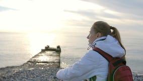 Νέα όμορφη γυναίκα στο σακάκι με τη συνεδρίαση σακιδίων πλάτης κοντά στη θάλασσα στο ηλιοβασίλεμα φιλμ μικρού μήκους