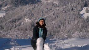 Νέα όμορφη γυναίκα στο χιονώδες δάσος βουνών είναι ευτυχής Η διασκέδαση κοριτσιών ρίχνει το χιόνι Παγωμένη ηλιόλουστη ημέρα κίνησ φιλμ μικρού μήκους