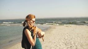 Νέα όμορφη γυναίκα τουριστών που περπατά στο νησί με το σκυλί chihuahua Θηλυκός περίπατος στην παραλία στην ηλιόλουστη ημέρα φιλμ μικρού μήκους