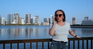 Νέα όμορφη γυναίκα το καλοκαίρι που στέκεται στην προκυμαία που μιλά στο τηλέφωνο απόθεμα βίντεο